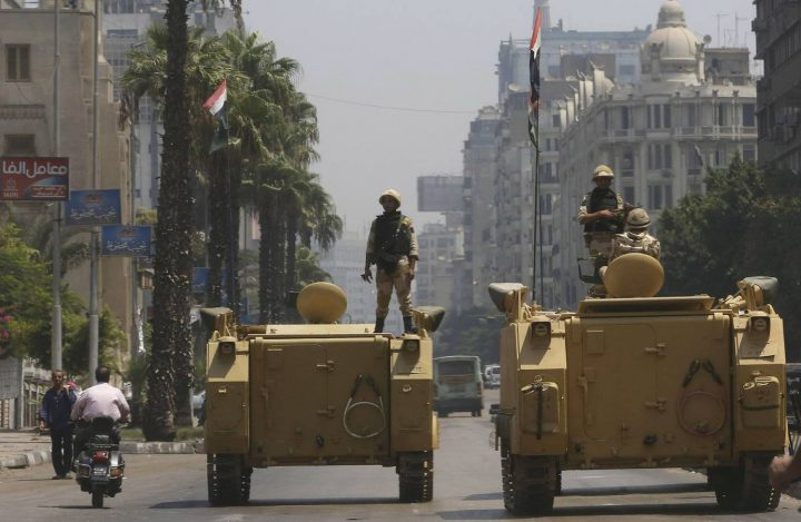 A soldier holds weapon as he stands on armoured personnel carrier positioned outside state-run television station in Cairo