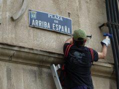 Un operario de la Ley de Memoria Histórica arranca una placa de la Plaza Arriba España