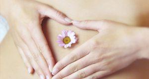 Mujer con sus manos en forma de corazón y una flor en el vientre