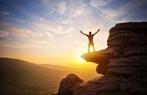 Hombre mirando al sol en la montaña