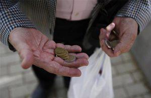 Hombre enseña las monedas en su mano