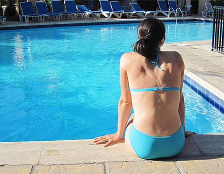 Mujer sola en la piscina de un hotel